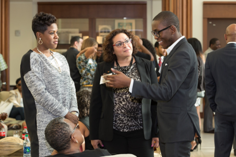 Two woman looking as a black man share thoughts in a suit